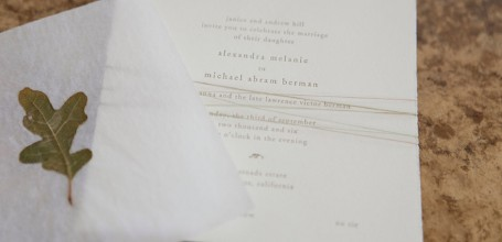 Hand-torn wedding invitation with leaf overlay