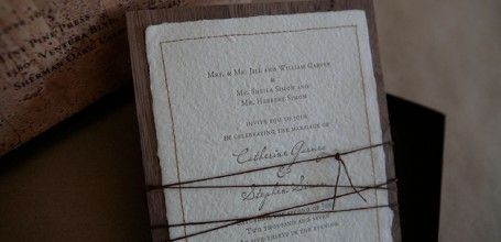 Handmade paper wedding invitation with stitched border and twine tie.
