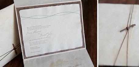 Handmade paper custom wedding invitation on wood with folder.